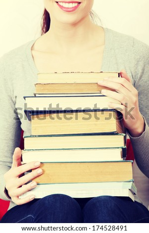 Happy woman holding pile of books on her knees  - stock photo