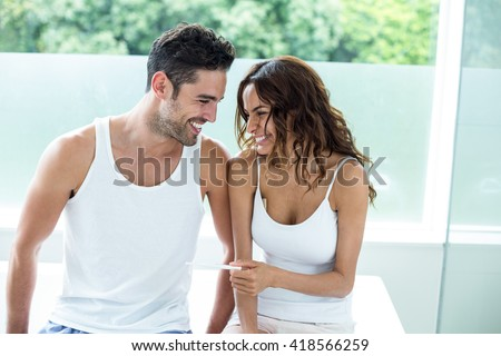 Happy woman holding pregnancy kit while sitting beside husband at home - stock photo