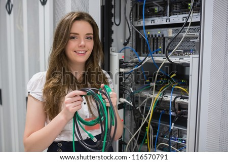 Happy woman holding server wires in data center - stock photo