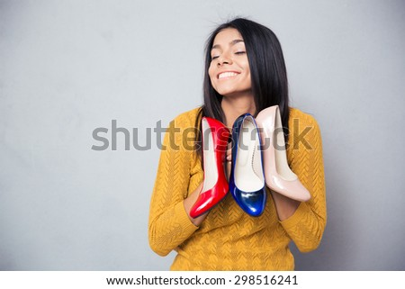 Happy woman holding shoes over gray background - stock photo