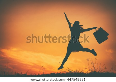 Happy Woman holding shopping bags jumping in sunset silhouette.Summer Vacation concept.Vintage Tone.