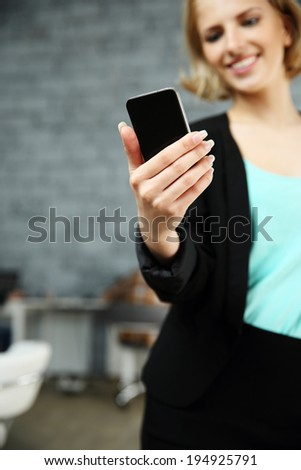 Happy woman holding smartphone in office. Focus on smartphone