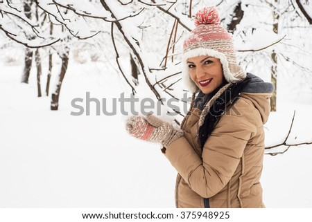 Happy woman holding snow in her hands with gloves - stock photo