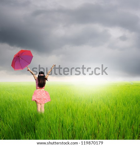 Happy Woman holding umbrella in rice fields and rainclouds