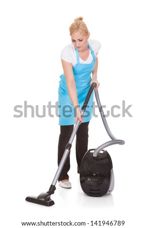 Happy Woman Holding Vacuum Cleaner Over White Background - stock photo