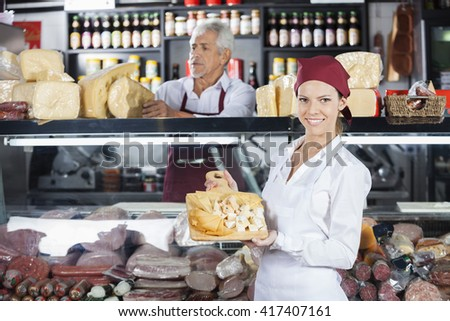 Happy Woman Holding Various Cheese On Board In Store - stock photo