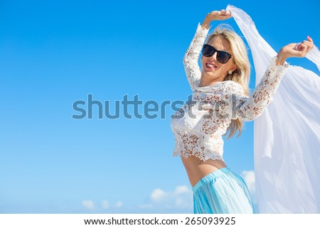 Happy woman holding white fabric on bright summer day with clear blue sky background - stock photo