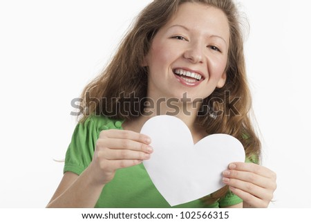 Happy woman holding white heart with two hands - stock photo