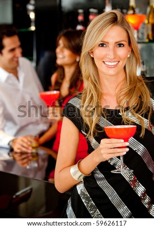 Happy woman in a bar or a nightclub having a drink - stock photo