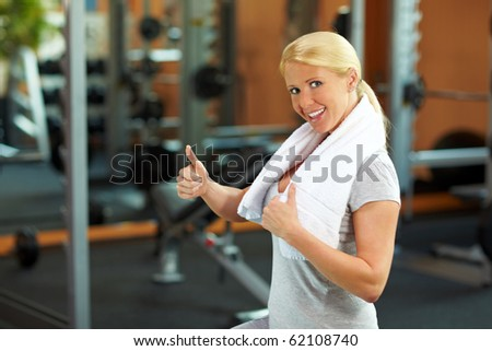 Happy woman in a gym holding her thumb up