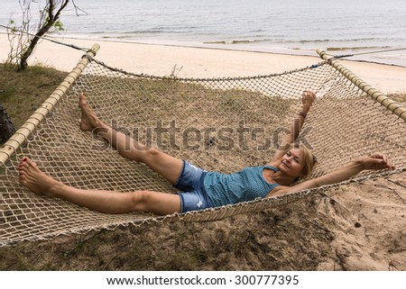 Happy woman in a hammock on the beach