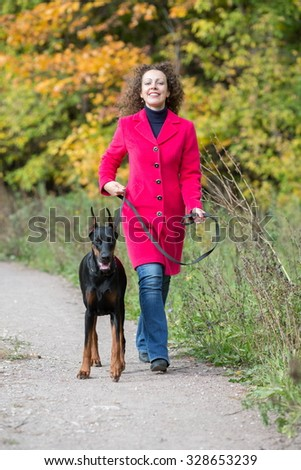 Happy woman in a red coat is walking with the black dog.
