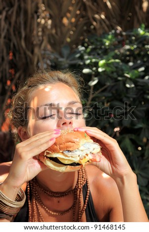Happy woman in a restaurant eating a fast food hamburger - stock photo