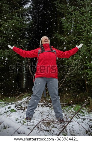 happy woman in a winter forest with falling snow. Portrait. - stock photo