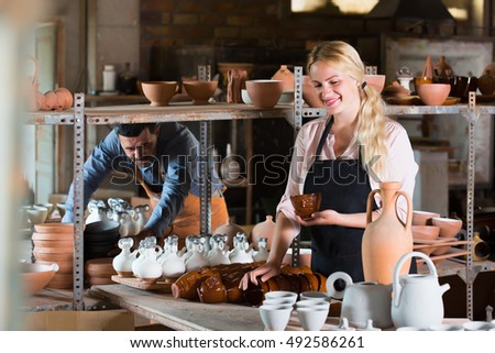 Happy woman in apron carrying ceramic vessels in atelier