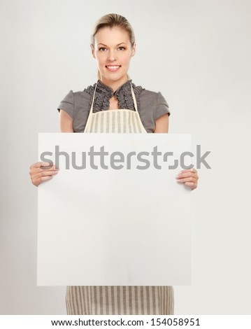 Happy woman in apron holding sign billboard - stock photo