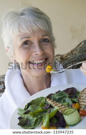 Happy woman in bathrobe eating salad - stock photo