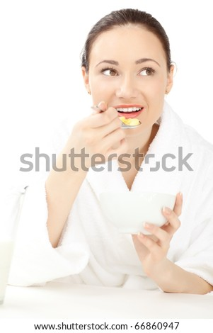 Happy woman in bathrobe holding bowl with cereals for breakfast
