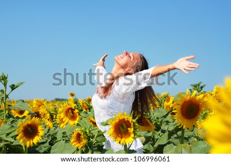 Happy woman in beauty field with sunflowers