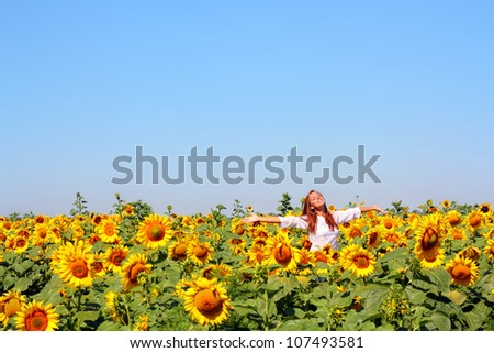 Happy woman in beauty field with sunflowers - stock photo