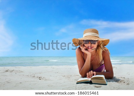 happy woman in bikini reading book on the beach - stock photo