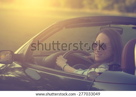 Happy woman in cabriolet car - stock photo