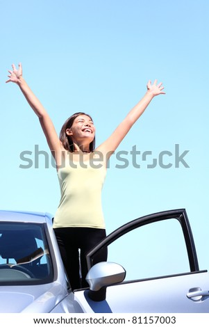 happy woman in car enjoying her freedom on vacation summer road trip. Beautiful young multiracial model - stock photo