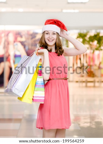happy woman in christmas hat with shopping bags In shopping mall