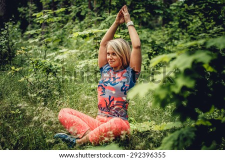 Happy woman in colorful clothes doing yoga in the forest.