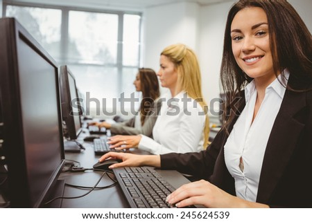 Happy woman in computer room smiling at camera in the office