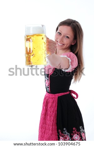 Happy woman in dirndl smiling in welcome as she offers a glass filled with a large refreshing pint of beer