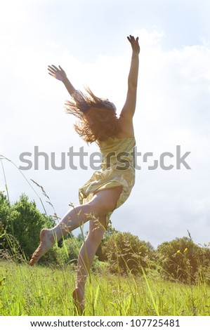 Happy woman in dress Jumping to the sky, shot from her back - stock photo