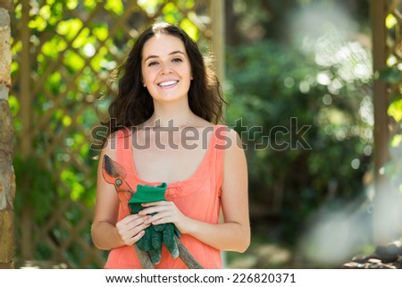 Happy  woman in dress with pruner in yard  of home - stock photo