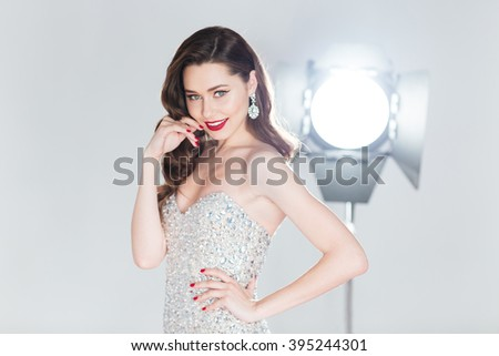 Happy woman in fashion dress posing with flash box on background - stock photo