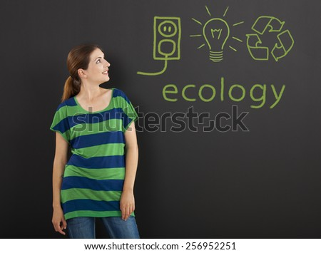 Happy woman in front of a chalkboard with ecology concepts written on it - stock photo