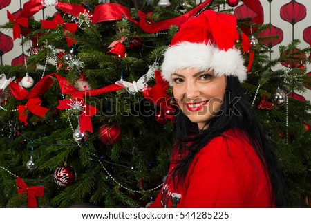 Happy woman in front of Christmas tree