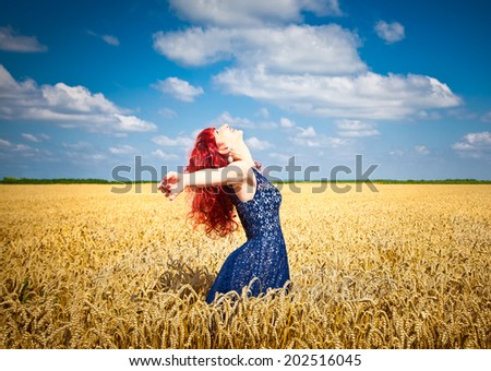 Happy woman in golden wheat in summer time. - stock photo