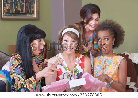 Happy woman in hair band holding gift box with friends - stock photo
