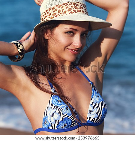 Happy woman in hat posing on blue sea background. Closeup portrait