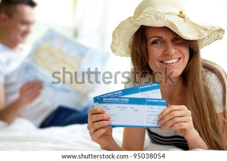 Happy woman in hat showing flight tickets - stock photo