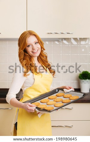 Happy woman in kitchen during cooking biscuits