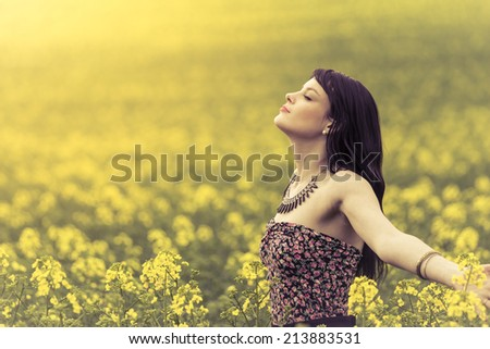 Happy woman in ocean of yellow flowers. Attractive genuine young girl enjoying the warm summer sun in a wide green meadow - stock photo