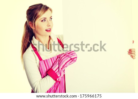 Happy woman in pink appron holding sign billboard. - stock photo