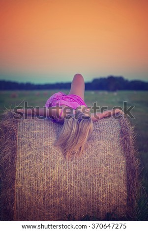 happy woman in pink dress posing  with hay in meadow field at evening time. toning photo - stock photo