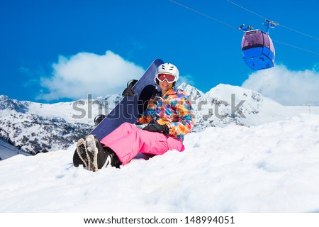 Happy woman in pink sit in snow with snowboard with cable car and mountains on blue sky background - stock photo