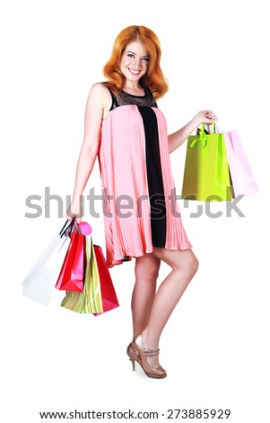 happy woman in pink summber dress smiling holding shopping bags