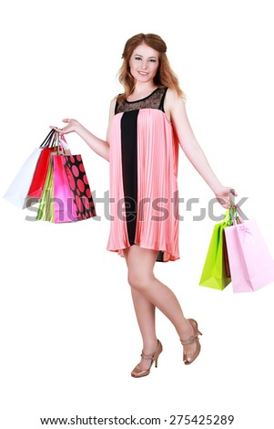 happy woman in pink summber dress smiling holding shopping bags - stock photo