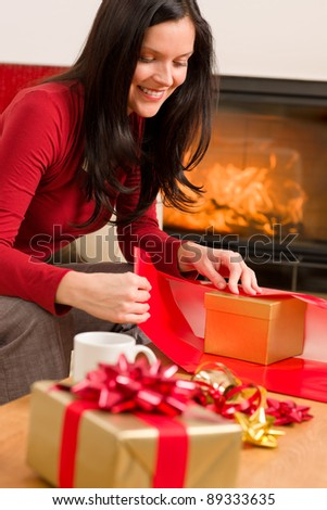 Happy woman in red wrapping Christmas present by home fireplace - stock photo