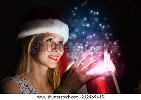 Happy woman in santa hat opening Christmas gift box