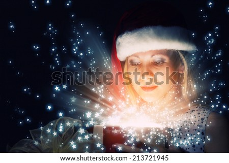 Happy woman in santa hat opening Christmas gift box - stock photo